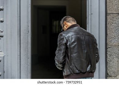 A mature man in leather jacket looks down attentively while he is on his back