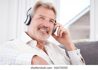 Mature Man Listening To Music On Wireless Headphones