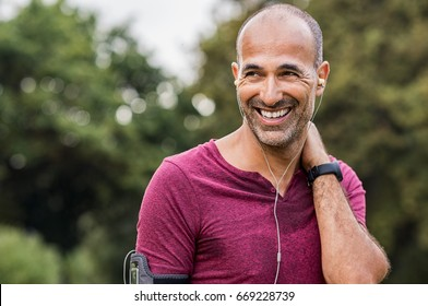 Mature man listening to music while resting after jogging. Happy senior man feeling refreshed after exercise. Portrait of a multiethnic man looking away in park while listening to music after fitness.
