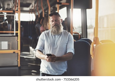 Mature man with a long beard standing on a bus smiling at a text messages on his cellphone during his morning commute