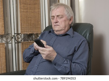 Mature man looking down at a phone looking annoyed and upset