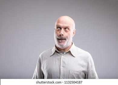 mature man looking guilty or having a smart idea