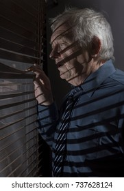 Mature man looking out of a window with blinds casting shadows