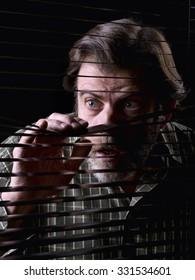Mature man looking through a window blind