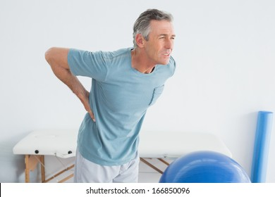 Mature man with lower back pain standing in the gym at hospital