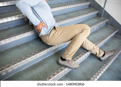Mature Man Lying On Staircase After Slip And Fall Accident