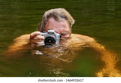 Mature man is making voyeurism from the surface of the water of the river with help of waterproof camera in his hands.