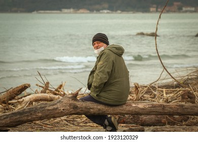 Mature man with mask and hat on the beach after the storm.