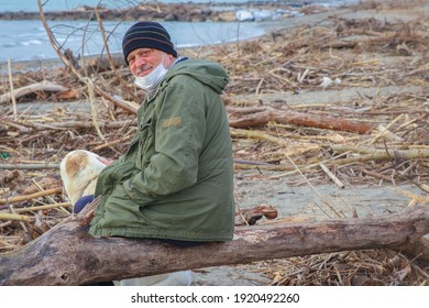 Mature man with mask and white dog on the beach after the storm