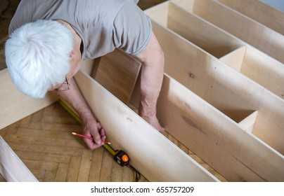 Mature man measuring wooden shelf with reel while making bookcase or shelf unit