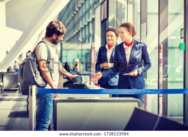 Mature man on board scanning his ticket on smartphone in airport
