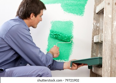 Mature man painting the wall with a roller while holding a paint can