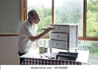 Mature man painting white furniture