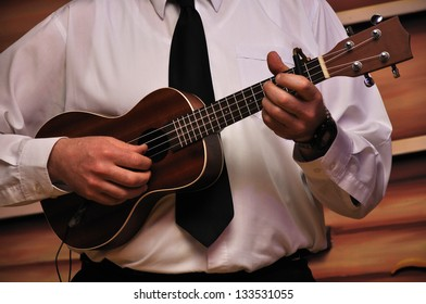 Mature man playing an electric ukelele in live stage performance