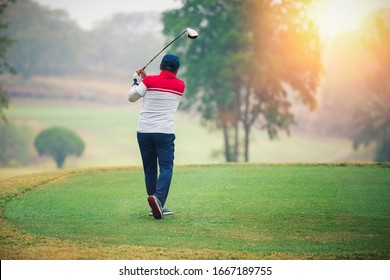 mature man playing golf on a golf course in the morning