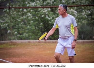 Mature man playing tennis