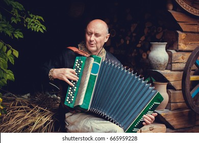 Mature man plays on a musical instrument accordion , is dressed in an embroidered shirt. Unification of the  Slavs on abroad