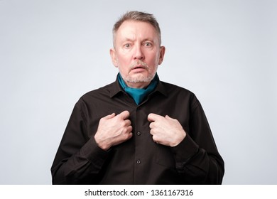 Mature man pointing to himself with question if he did something wrong.