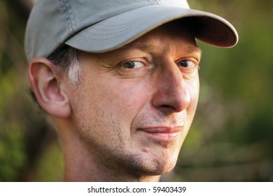 Mature man portrait with expressive naughty eyes and cap on