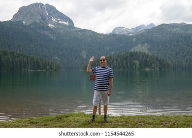 Mature man is posing with hi gesture on background of glacial Black Lake in Durmitor National UNESCO park near Zabljak town, Montenegro.