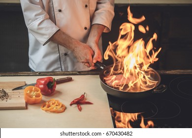 Mature man professional chef cooking meal indoors