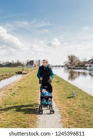 Mature man pushing baby stroller - Hindeloopen, Friesland, Netherlands, Europe
