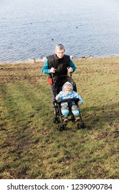 Mature man pushing stroller with toddler girl uphill the dyke – Hindeloopen, Netherlands, Europe
