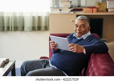 Mature man reading e-book when sitting on sofa