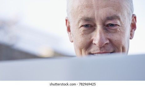 Mature man reading something on his laptop and smiling
