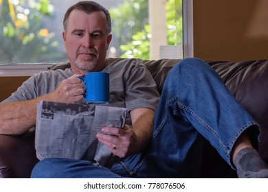 Mature man relaxes and reads the paper on leather chair