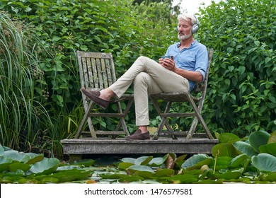 Mature Man Relaxing In Garden Listening To Music On Wireless Headphones On Jetty By Lake