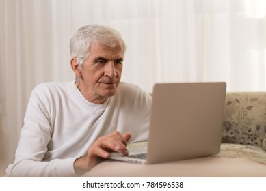 Mature man relaxing on the sofa and  typing an e-mail on laptop