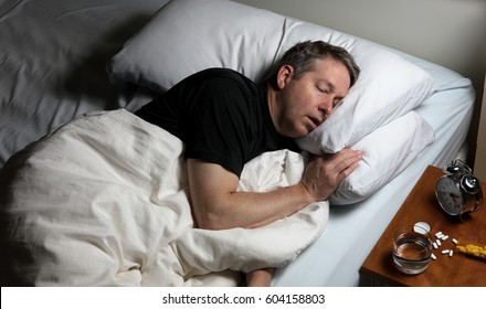 Mature man resting head in pillow while trying to sleep in bed. Insomnia concept with pain medicine on nightstand.