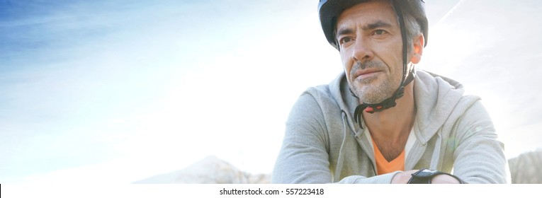 Mature man riding bike in the mountain, template