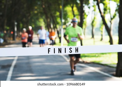 Mature man running towards the finish line