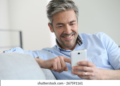 Mature man sending message with smartphone