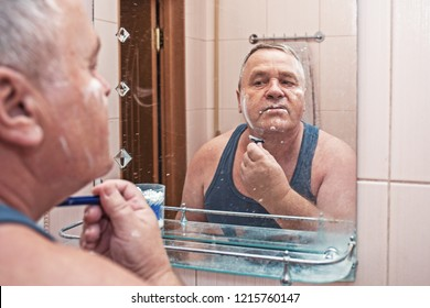 Mature man shaves in bathroom in morning, reflection in mirror portrait, close up