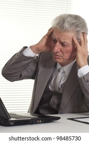 mature man sitting at the computer on a light