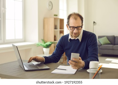 Mature man sitting at office work desk with laptop and notebook, using smart business organizer on mobile phone, reading good news, text messaging online, or getting easy access to data backup service