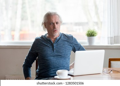Mature man sitting on chair at table working on computer feels sudden injury acute lower back pain after long hours of work at home. Health problems wrong bad posture and sedentary lifestyle concept