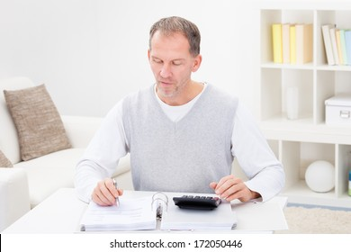 Mature Man Sitting On Couch At Home Holding Calculator And Bills