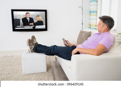 Mature Man Sitting On Sofa With Remote Holding In Hand Watching Television At Home