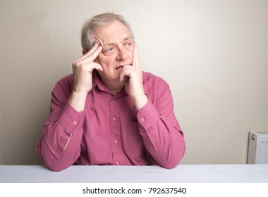 Mature man sitting at a table looking confused and worried