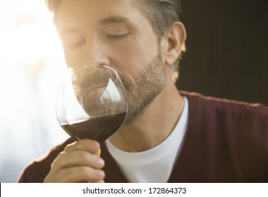 Mature man smelling glass of red wine at home