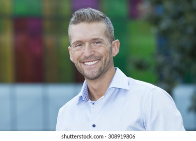 Mature Man Smiling At The Camera. He is outside of the office