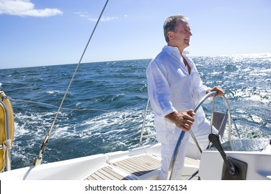 Mature man standing at helm of yacht out at sea, steering, smiling, side view (tilt)