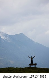 Mature man standing on bench in mountains of Austria with arms outstretched