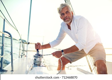 Mature man standing on the deck of his boat using a winch while out for a sail on a sunny afternoon