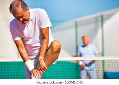 Mature man standing while suffering from leg pain during match at tennis court