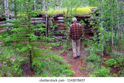 Mature man stands in front of a ramshackle trapper's cabin in the Alaskan wilderness.  Cabin has moss growing over the top of it.